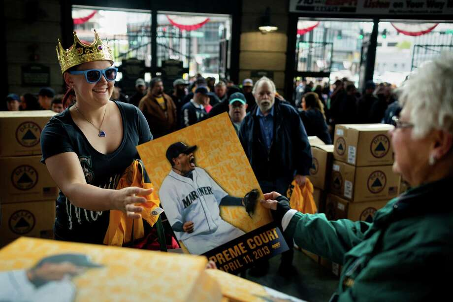 Hannah Sauget, 19, left, collects her free Felix Hernandez sign and T-shirt before a game against the Texas Rangers Thursday, April 11, 2013, at Safeco Field in Seattle. The Rangers beat the Mariners 4-3. The evening marked Felix Hernandez's opening game pitching at home for the 2013 season. The first 25,000 fans to arrive at Safeco Field were given discounted tickets and King Felix shirts. Photo: JORDAN STEAD / SEATTLEPI.COM
