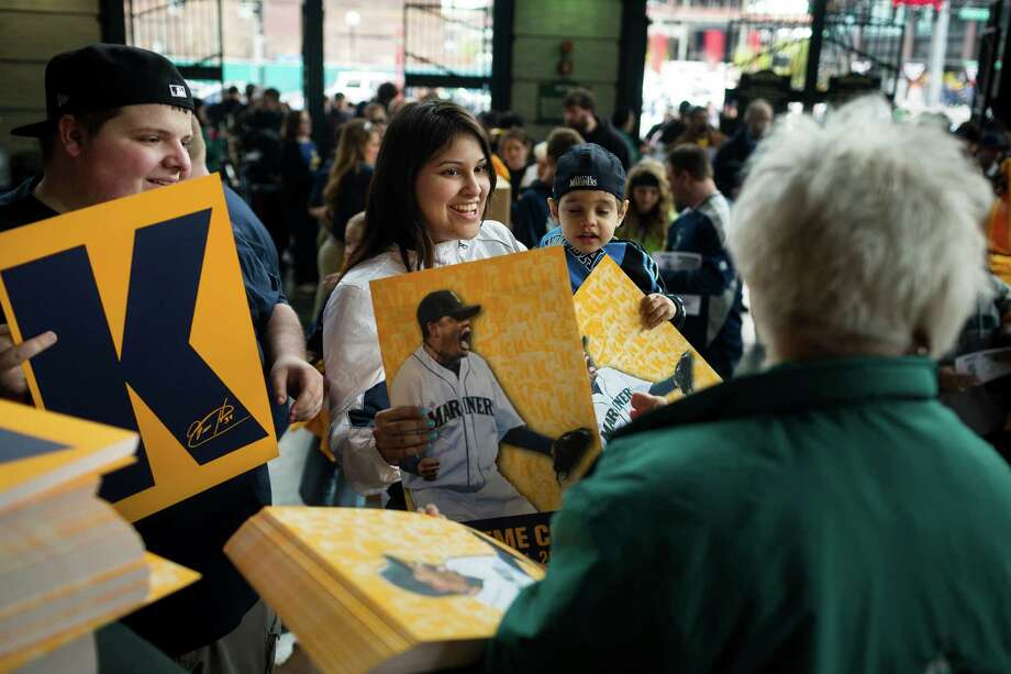 Mariners fans stream into the stadium to collect free signs and T-shirts before a game against the Texas Rangers Thursday, April 11, 2013, at Safeco Field in Seattle. The Rangers beat the Mariners 4-3. The evening marked Felix Hernandez's opening game pitching at home for the 2013 season. The first 25,000 fans to arrive at Safeco Field were given discounted tickets and King Felix shirts. Photo: JORDAN STEAD / SEATTLEPI.COM