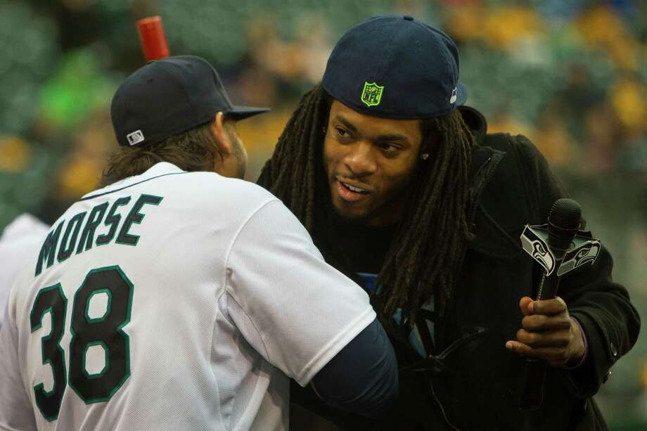 Before throwing out the first pitch, Seattle Seahawks player Richard Sherman, right, gives Mariners player Michael Morse, left, a hug at a game against the Texas Rangers Thursday, April 11, 2013, at Safeco Field in Seattle. The Rangers beat the Mariners 4-3. The evening marked Felix Hernandez's opening game pitching at home for the 2013 season. The first 25,000 fans to arrive at Safeco Field were given discounted tickets and King Felix shirts. Photo: JORDAN STEAD / SEATTLEPI.COM