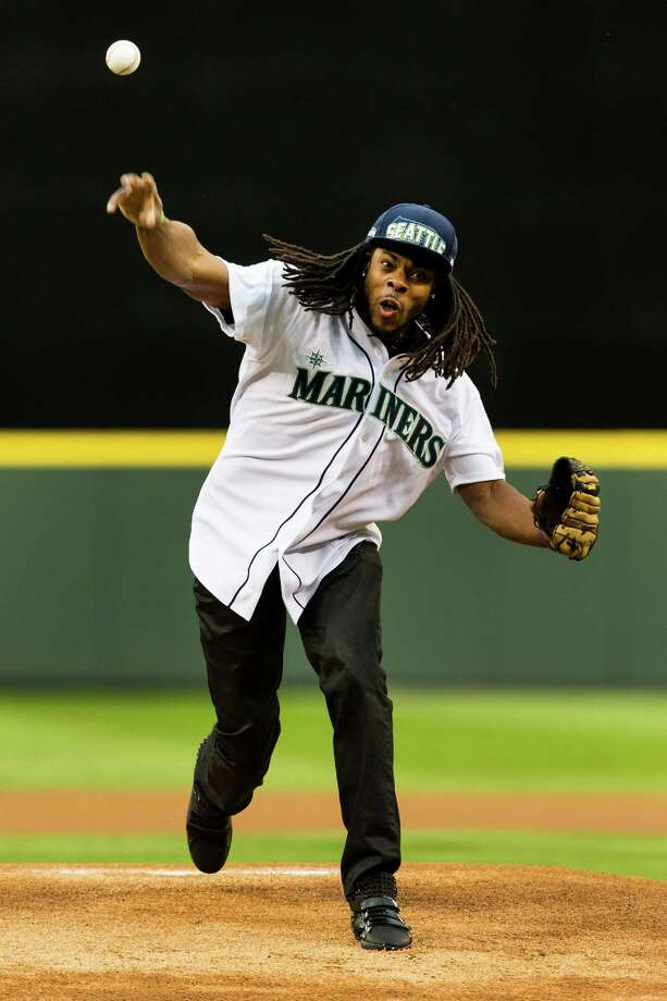 Seattle Seahawks player Richard Sherman throws out an eager first pitch at a Mariners game against the Texas Rangers Thursday, April 11, 2013, at Safeco Field in Seattle. The Rangers beat the Mariners 4-3. The evening marked Felix Hernandez's opening game pitching at home for the 2013 season. The first 25,000 fans to arrive at Safeco Field were given discounted tickets and King Felix shirts. Photo: JORDAN STEAD / SEATTLEPI.COM