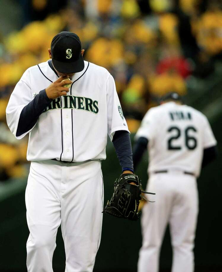 Mariners pitcher Felix Hernandez, left, kisses the first baseball in the moments before the start of a game against the Texas Rangers Thursday, April 11, 2013, at Safeco Field in Seattle. The Rangers beat the Mariners 4-3. The evening marked Felix Hernandez's opening game pitching at home for the 2013 season. The first 25,000 fans to arrive at Safeco Field were given discounted tickets and King Felix shirts. Photo: JORDAN STEAD / SEATTLEPI.COM