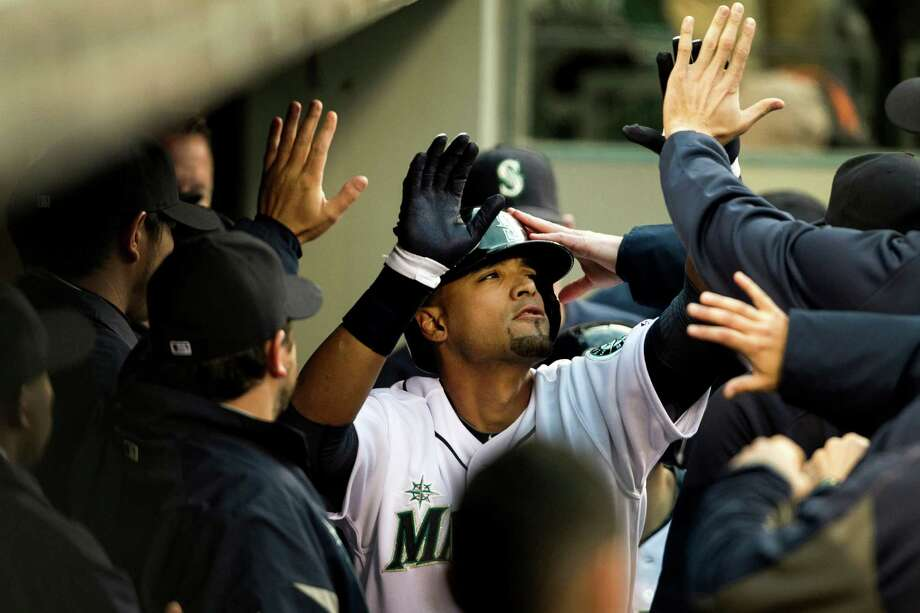Franklin Gutierrez, center, of the Seattle Mariners, is congratulated by his team after scoring the first run of a game against the Texas Rangers Thursday, April 11, 2013, at Safeco Field in Seattle. The Rangers beat the Mariners 4-3. The evening marked Felix Hernandez's opening game pitching at home for the 2013 season. The first 25,000 fans to arrive at Safeco Field were given discounted tickets and King Felix shirts. Photo: JORDAN STEAD / SEATTLEPI.COM