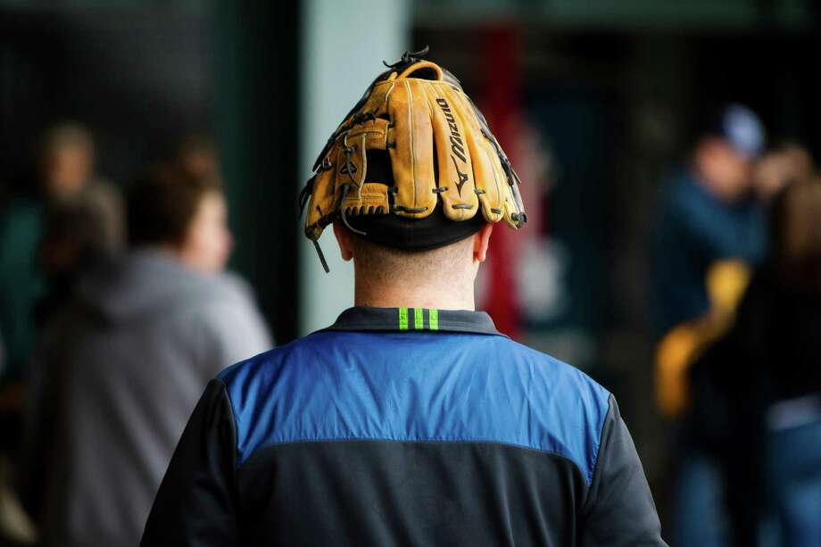 While some fans stuck to the outfield to catch balls, one man used his mitt as a hat while walking around the stadium before a Mariners game against the Texas Rangers Thursday, April 11, 2013, at Safeco Field in Seattle. The Rangers beat the Mariners 4-3. The evening marked Felix Hernandez's opening game pitching at home for the 2013 season. The first 25,000 fans to arrive at Safeco Field were given discounted tickets and King Felix shirts. Photo: JORDAN STEAD / SEATTLEPI.COM