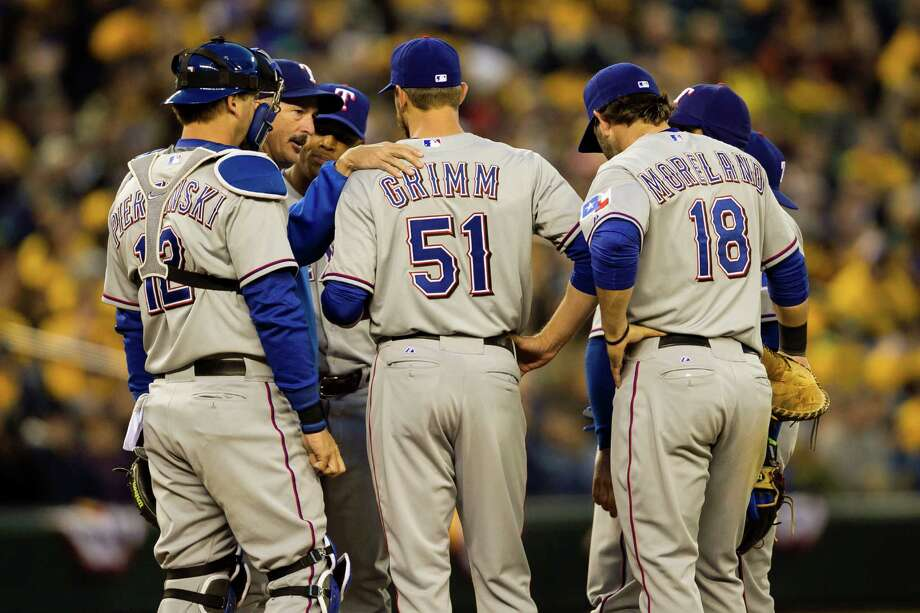 Texas Rangers players chat at the mound during a game against the Mariners Thursday, April 11, 2013, at Safeco Field in Seattle. The Rangers beat the Mariners 4-3. The evening marked Felix Hernandez's opening game pitching at home for the 2013 season. The first 25,000 fans to arrive at Safeco Field were given discounted tickets and King Felix shirts. Photo: JORDAN STEAD / SEATTLEPI.COM