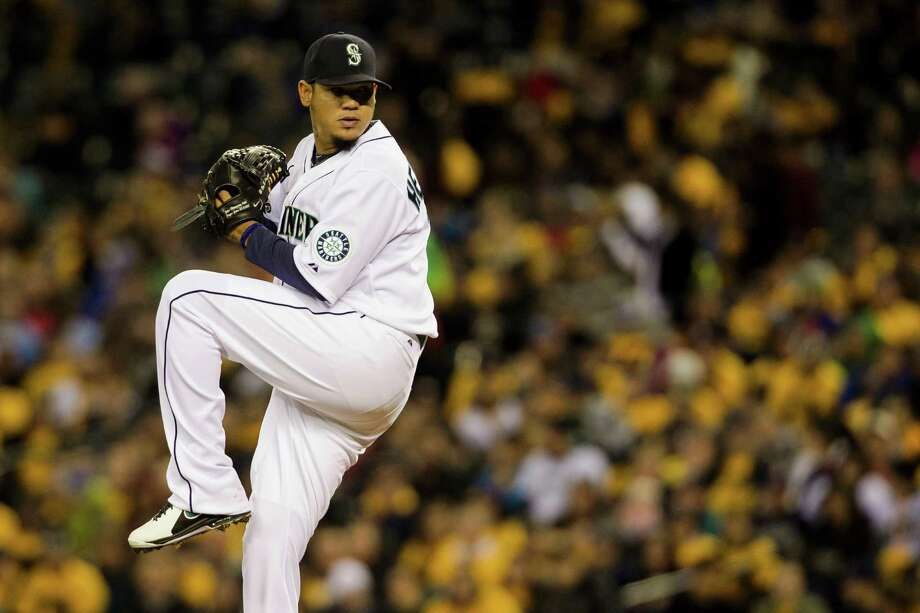 Backed by a sea of yellow shirts, Mariners pitcher Felix Hernandez, center, pitches during a game against the Texas Rangers Thursday, April 11, 2013, at Safeco Field in Seattle. The Rangers beat the Mariners 4-3. The evening marked Felix Hernandez's opening game pitching at home for the 2013 season. The first 25,000 fans to arrive at Safeco Field were given discounted tickets and King Felix shirts. Photo: JORDAN STEAD / SEATTLEPI.COM