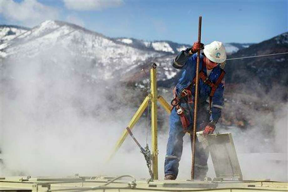 "A worker checks a dipstick to check water levels and temperatures in a series of tanks at an Encana Oil & Gas (USA) Inc. hydraulic fracturing operation at a gas drilling site outside Rifle, Colorado. Hydraulic fracturing, or ""fracking,"" can greatly increase the productivity of an oil or gas well by splitting open rock with water, fine sand and lubricants pumped underground at high pressure. Companies typically need several million gallons of water to frack a single well. In western Colorado, Encana says it recycles over 95 percent of the water it uses for fracking to save money and limit use of local water supplies. Photo: Brennan Linsley, AP / AP"