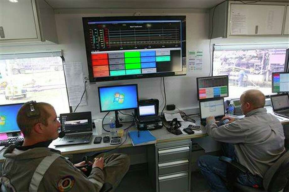 "Technicians inside a trailer direct the pressure and mix of water and chemicals pumped into an Encana Oil & Gas (USA) Inc. well during hydraulic fracturing, outside Rifle, in western Colorado. Hydraulic fracturing, or ""fracking,"" raises concern among some that the chemicals used and hydrocarbons released can contaminate groundwater. Industry officials say an absence of documented, widespread problems with fracking proves the process is safe. Photo: AP"