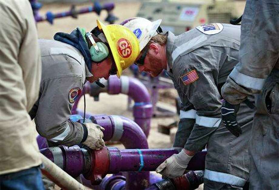 Workers adjust piping during a short pause in water pumping during a natural gas hydraulic fracturing operation at an Encana Oil & Gas (USA) Inc. drilling site outside Rifle, in western Colorado. The first experimental use of hydraulic fracturing was in 1947, and more than 1 million U.S. oil and gas wells have been fracked since, according to the American Petroleum Institute. The National Petroleum Council estimates up to 80 percent of natural gas wells drilled in the next decade will require hydraulic fracturing. Photo: Brennan Linsley, AP / AP