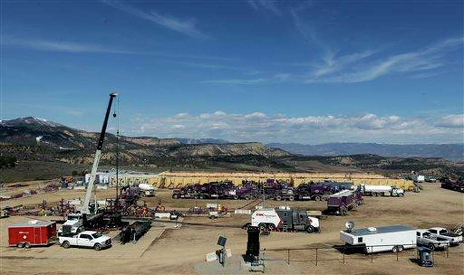 "A hydraulic fracturing operation is underway at a site outside Rifle, in western Colorado. In the background, a battery of yellow tanks hold water for the job at an Encana Oil & Gas (USA) Inc. gas well. Pump trucks are parked in front of the tanks. Workers control the flow of water, sand and chemicals into the well heads, left, from an operations trailer, center far right. Hydraulic fracturing, or ""fracking,"" raises concern among some that the chemicals used and hydrocarbons released can contaminate groundwater. Industry officials say an absence of documented, widespread problems with fracking proves the process is safe. Photo: AP"