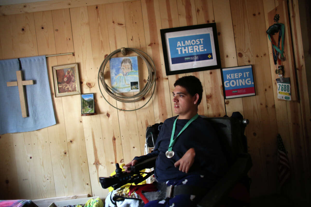 Terry Hoefer sits in his motorized wheelchair in his bedroom near Gig Harbor on March 27, 2013. Hoefer plans to compete in the Rock 'n' Roll  Seattle Half Marathon on June 22.