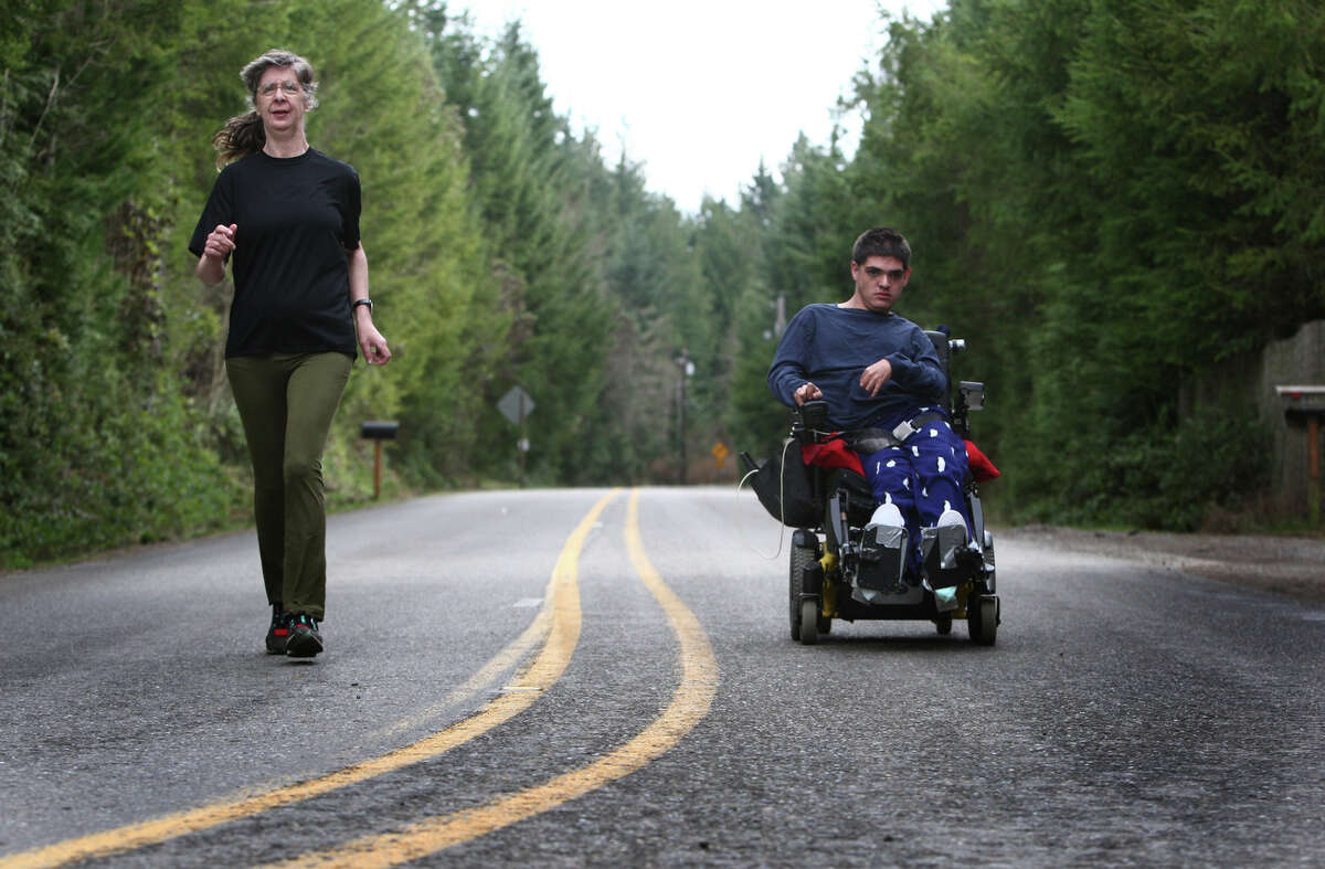 Vickie Hoefer, left, runs alongside her son Terry Hoefer in his motorized wheelchair on a rural road near their Gig Harbor-area home on March 27, 2013. Hoefer wanted to compete in the Rock 'n' Roll Seattle Half Marathon on his chair, and this year the race's new course has less hills.