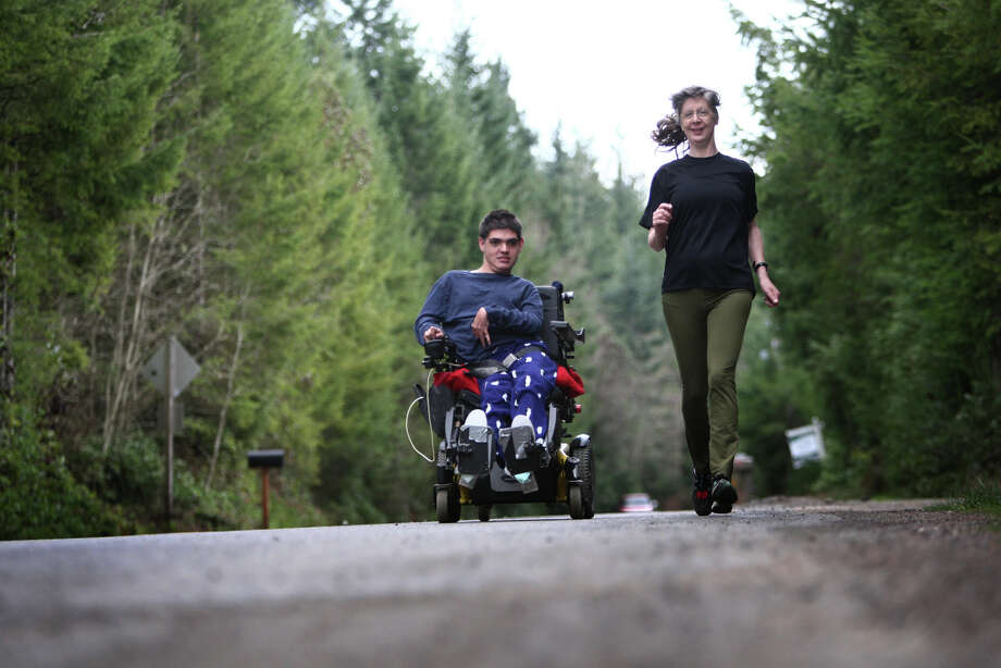 Vickie Hoefer runs alongside her son Terry Hoefer in his 