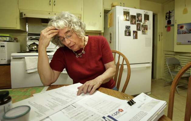 Carol Patterson reviews records on energy improvements she made to her home. The projects earned her about $2,000 credit on her CPS Energy bills. Photo: Bob Owen / San Antonio Express-News