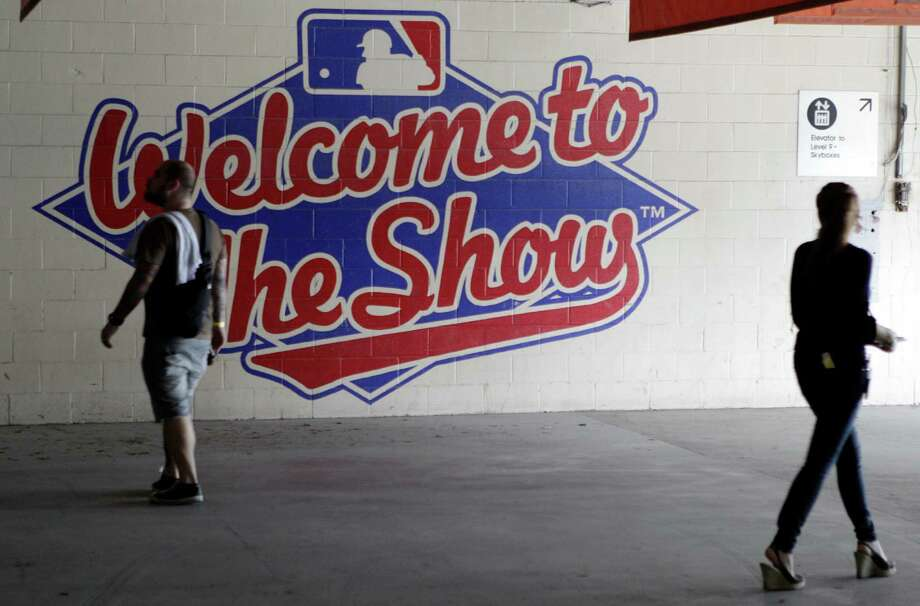 People walk past a Major League Baseball wall display during a tour inside the Reliant Astrodome Tuesday, April 3, 2012, in Houston. Photo: Melissa Phillip, Houston Chronicle / © 2012 Houston Chronicle