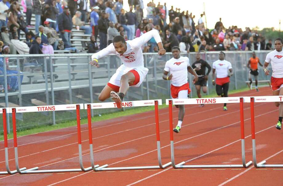 Memorial Titan hurdler Jammil Peeples, left, clears the last hurdle in the 300-Meter Hurdle event where he finished first.  The 21-5A track meet finals were held Thursday night at the Port Arthur Auxiliary Stadium in Port Arthur. Dave Ryan/The Enterprise Photo: Dave Ryan