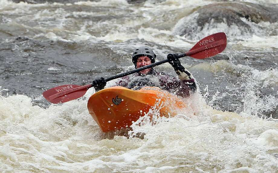 Whitewater rush: Curt Crittenden kayaks down the swollen Contoocook River in Henniker, N.H. Photo: Jim Cole, Associated Press