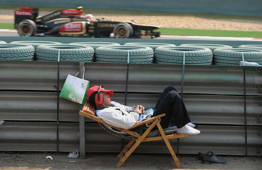 Some people can sleep through anything: A track marshal naps as Lotus driver Kimi Raikkonen of Finland roars past at 200+ mph during a practice session for the Formula One Chinese Grand Prix in Shanghai. Photo: Peter Parks, AFP/Getty Images