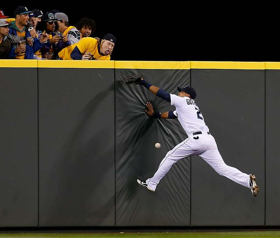 Look out below! The Mariners' Franklin Gutierrez might have made this catch if it weren't for the strange fan who looks like he's about to throw up. (Safeco Field in Seattle.) Photo: Otto Greule Jr, Getty Images
