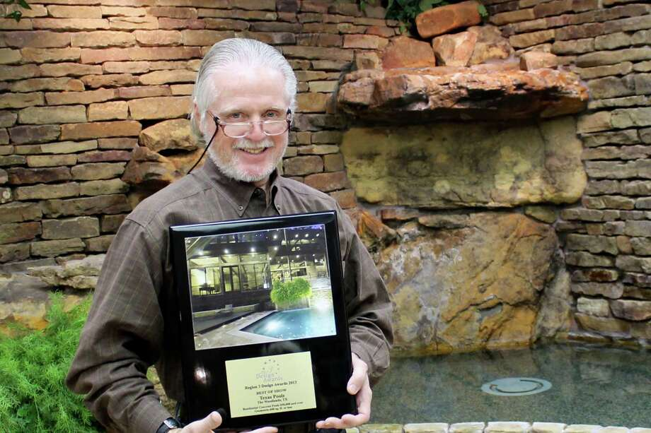 Paul Ryan, president of Texas Pools, shows off the best in show award for the winning pool.