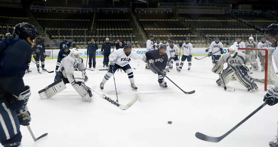 Yale players work on a drill between goaltenders Jeff Malcolm, left, and Nick Maricic, right, during NCAA college hockey practice at the Frozen Four on Friday, April 12, 2013, in Pittsburgh. Yale takes on Quinnipiac on the championship game on Saturday. Photo: Keith Srakocic