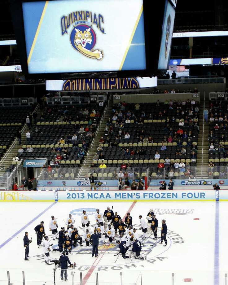 Quinnipiac players and coaching staff gather at center ice during NCAA college hockey practice at the Frozen Four, Friday, April 12, 2013, in Pittsburgh. Quinnipiac plays Yale in the championship game on Saturday. Photo: Keith Srakocic