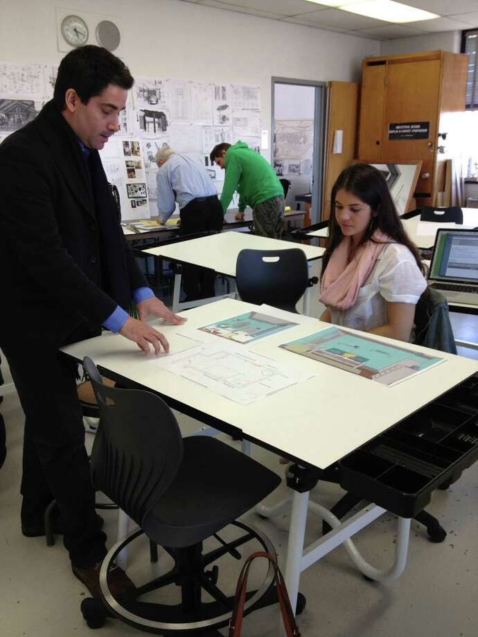 "University of Bridgeport professor Giancarlo Massaro instructs one of his interior design students, ""Sam"" Finch, on a project with Her Haven, a nonprofit Monroe-based organization, that creates special spaces and home sanctuaries for special women in the community. The university and Her Haven are joining forces to host an open house April 24 from 6 to 8 p.m. on campus. Photo: Contributed Photo"