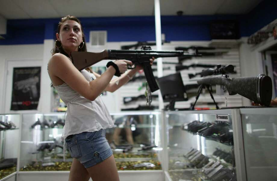 A woman tries out a firearm at a gun sale in Pompano Beach, Fla. The U.S. Senate is close to voting on background checks for purchasers of firearms. How the proposal will emerge after amendments, etc., is anybody's guess. Photo: Joe Raedle, Getty Images