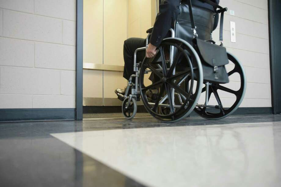 Man in wheelchair getting into elevator Photo: Jupiterimages, (stock Photography) / Comstock Images