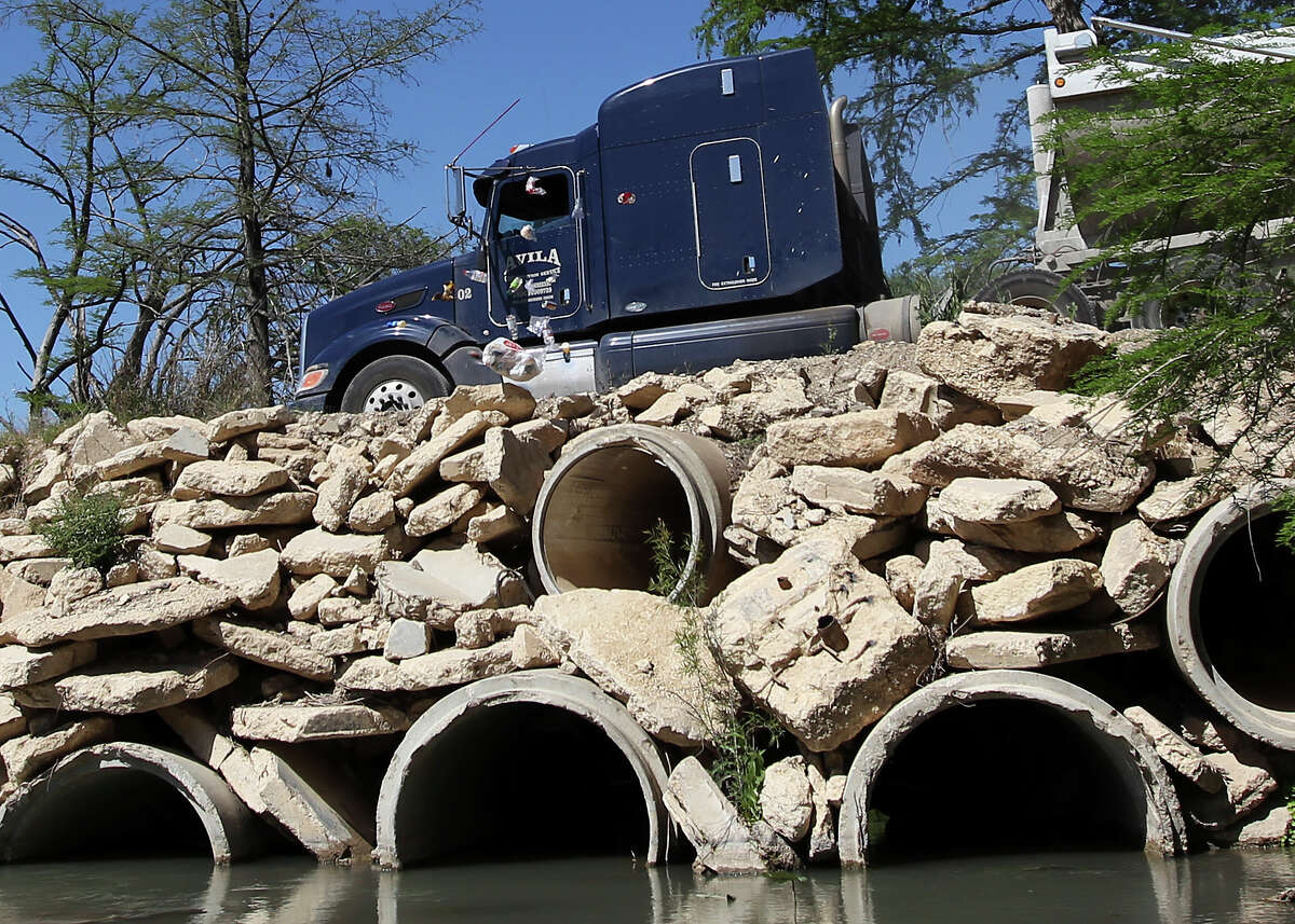 A truck driver tosses trash out his window as he drives over a bridge on the Medina River that connects properties owned by Charles Timms in South Bexar County on Thursday, April 11, 2013. San Antonio River Authority, which owns the bed and banks of the river, has notified Timms that his bridge is an encroachment and has to be removed.