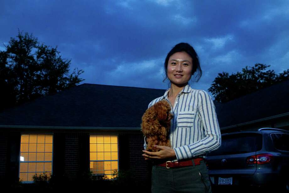 Faye Liu, holds her dog, Toffee, as she stands in front of the home she rents, Wednesday, April 3, 2013, in Houston. Faye Liu and her husband is Jiang Wu moved to Houston last September for Faye's job as a geologist at a Houston energy company and they're looking to buy a house in the Energy Corridor. Jiang, 35, works in the Texas Medical Center and they both moved here from Bloomington, Indiana after getting their PhDs from Indiana University. There are few houses that come up for sale, and when they do, they go fast. They're competing with cash buyers who have an advantage because it's easier for the seller to close. They've upped their budget from $200,000 to more than $330,000. (Cody Duty / Houston Chronicle) Photo: Cody Duty, Staff / © 2013 Houston Chronicle