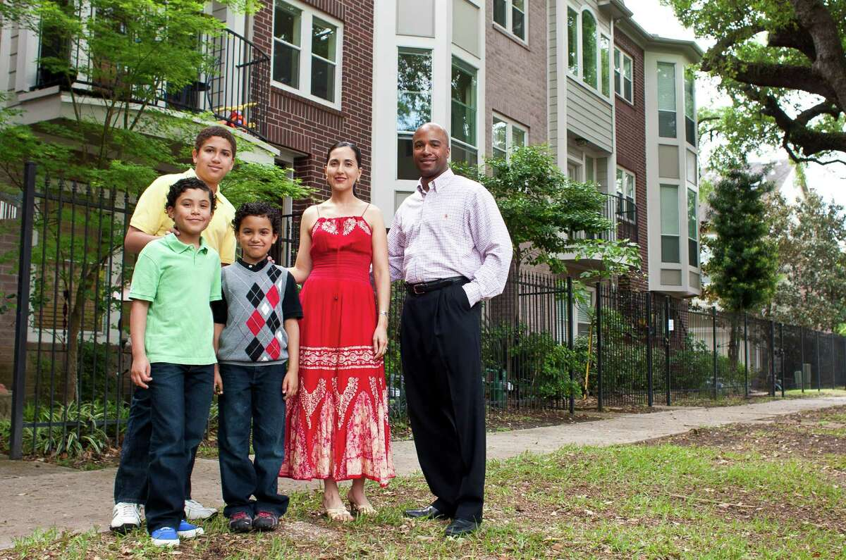 The Lewis Family, Miles Lewis, 13, Marcus Lewis, 10, Mateo Lewis, 7, Cynthia Aceves-Lewis, and Michael Lewis stand in front of their Midtown home, where they lived for 14-years, Sunday, April 7, 2013, in Houston. The Lewis family is looking into moving to the suburbs so their kids will have more space to play. ( Nick de la Torre / Chronicle )