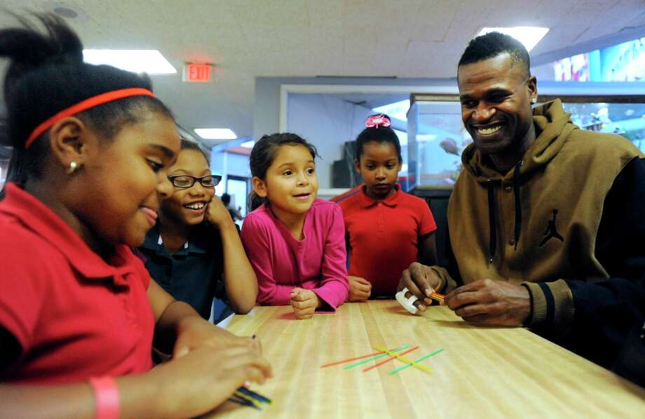 Stephen Jackson of the Spurs, right, plays a game of Pick Up Sticks with Janiah Perkins, 8, left, at the Eastside Branch of the Boys & Girls Club on Wednesday, Nov. 28. Jackson and teammate Kawhi Leonard visited the club. Photo: Billy Calzada, San Antonio Express-News / SAN ANTONIO EXPRESS-NEWS
