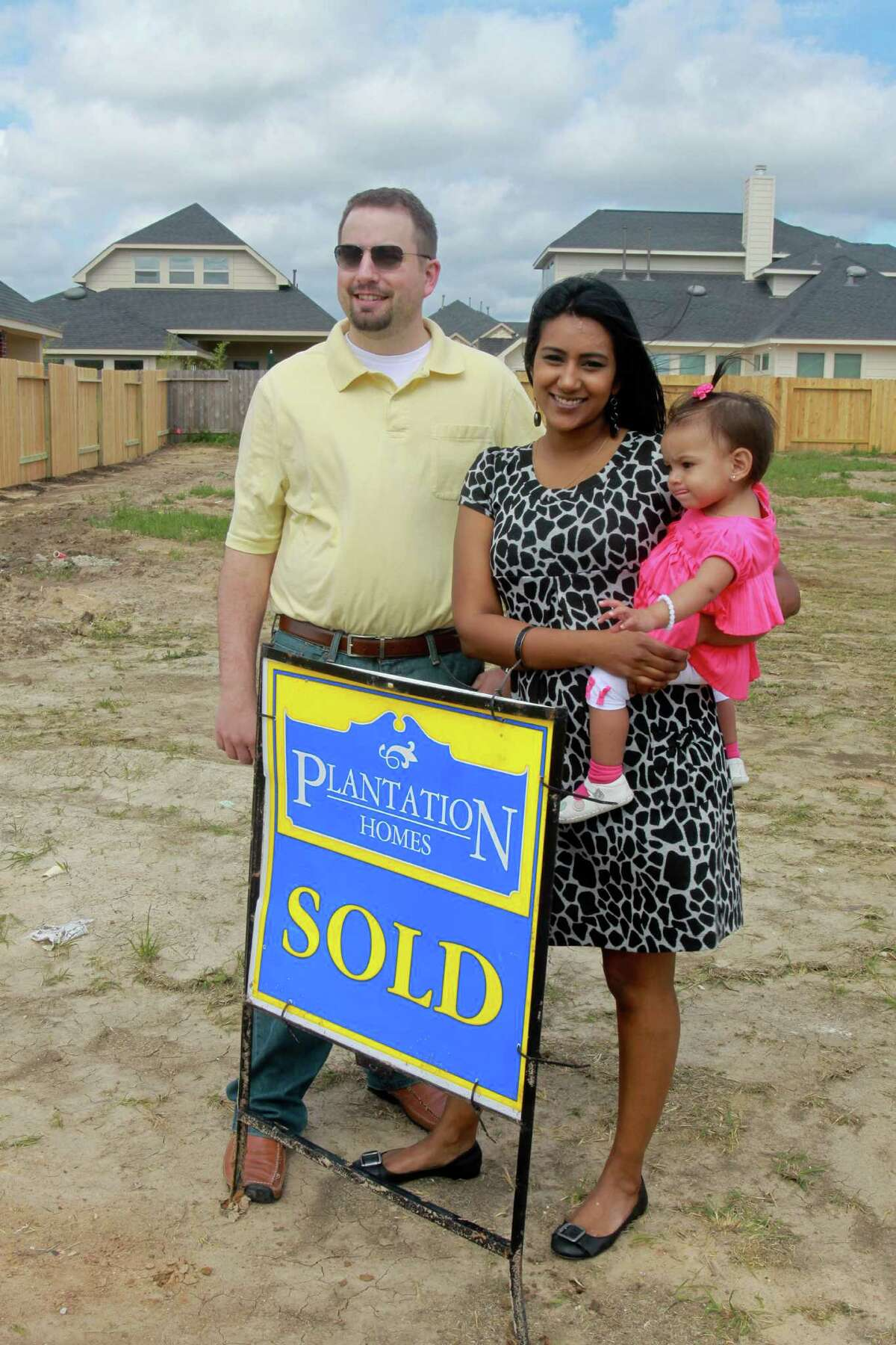 (For the Chronicle/Gary Fountain, April 5, 2013) David and Saritha Bowles, with their daughter Sita, eleven-months-old, at the location of their new home. Construction doesn't start for a few weeks. They spent nearly three months looking at about thirty homes before deciding on a new build in Rosenberg.