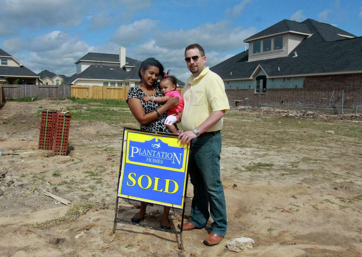(For the Chronicle/Gary Fountain, April 5, 2013) Saritha and David Bowles, with their daughter Sita, eleven-months-old, at the location of their new home. Construction doesn't start for a few weeks. They spent nearly three months looking at about thirty homes before deciding on a new build in Rosenberg.