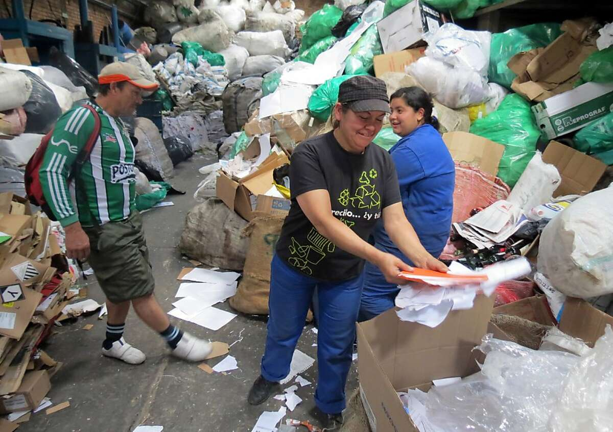 Blanca Cecilia Lopez, center, sorts paper for recycling in the Pensilvania recycling facility in Bogota, Colombia