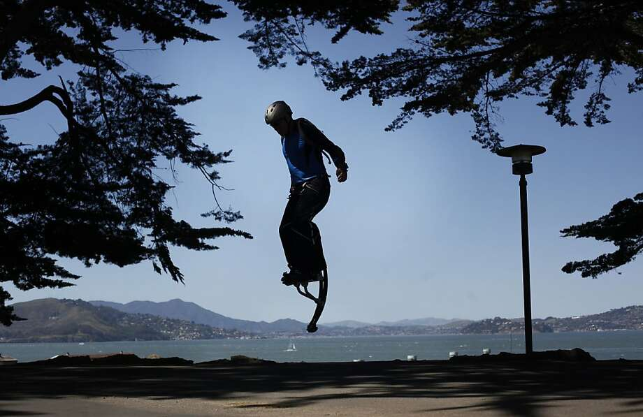 Wearing his jumping stilts, Rico Trias, 45, jumps on top of the hill at Fort Mason in San Francisco. Photo: Mike Kepka, The Chronicle