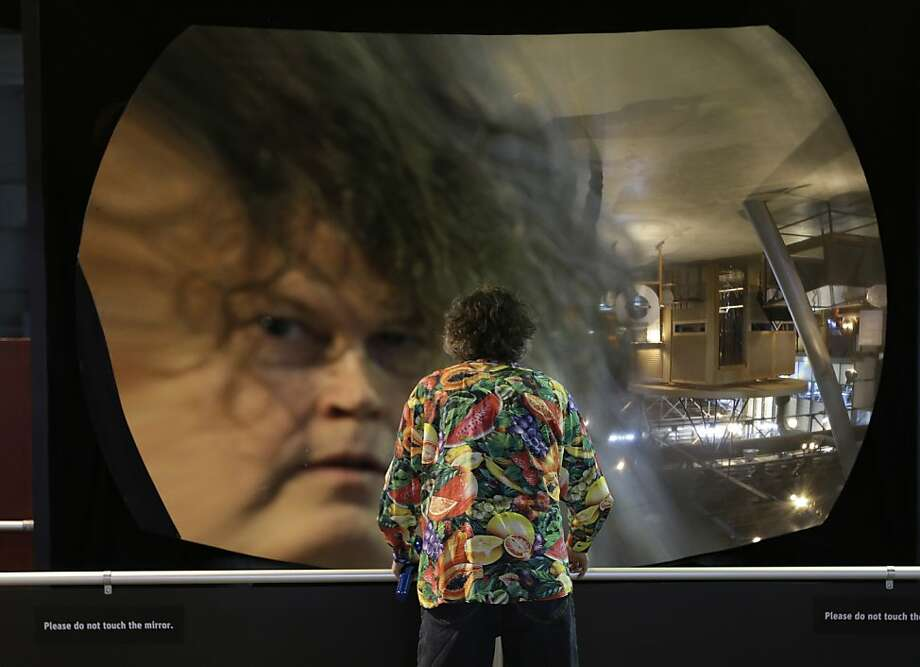 Richard Brown peers at his head reflected in the parabolic mirror - a showstopper at the new Exploratorium site. Photo: Eric Risberg, Associated Press