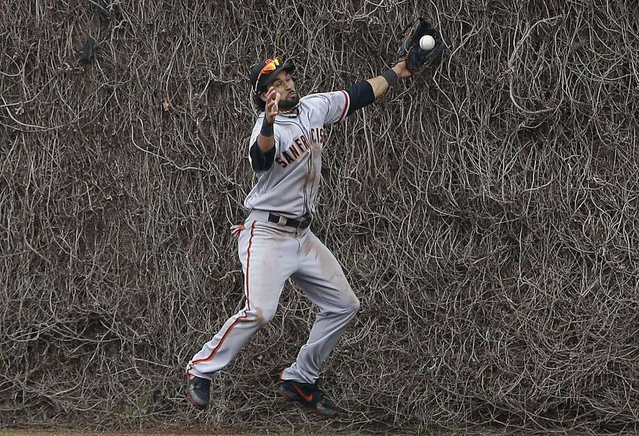 Angel Pagan goes into the wall as Starlin Castro's game-winning double bounces off the wall toward his glove. Photo: Nam Y. Huh, Associated Press