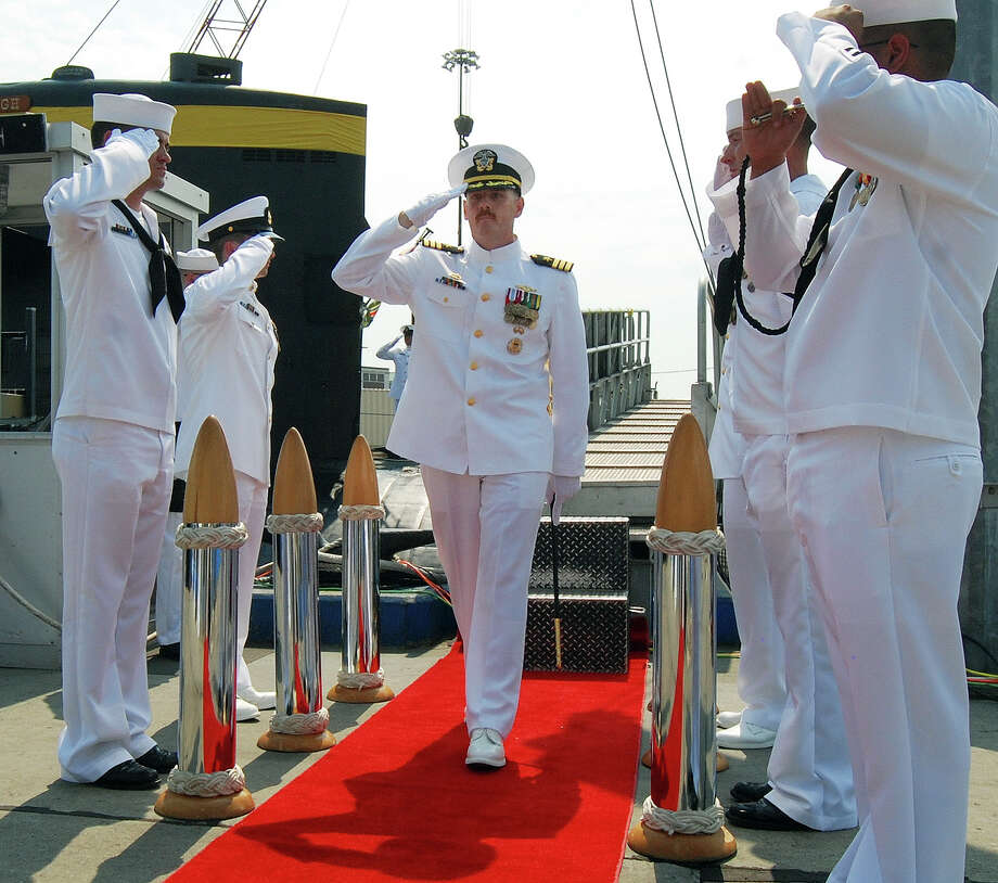 In this Aug. 3, 2012 photo provided by the U.S. Navy, Cmdr. Michael P. Ward II, center, is saluted during the change-of-command ceremony for the nuclear submarine USS Pittsburgh at the Naval Submarine Base New London, in Groton, Conn.  Ward was relieved of his command in August 2012 after he faked his own death to end an affair with a woman. Ward's lawyer said Friday, April 12, 2013, during a hearing in Groton to determine his status with the Navy, that Ward admits to the mistake and apologizes, and that he should not be expelled from the Navy. (AP Photo/U.S. Navy, Jason J. Perry ) Photo: Jason J. Perry, HOPD / U.S. Navy