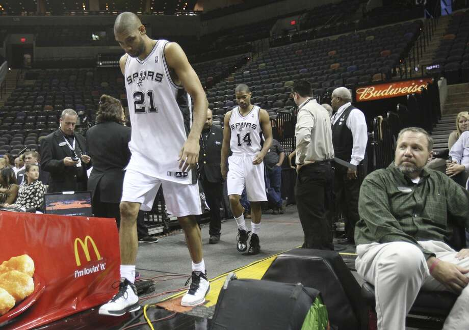 Spurs\' Tim Duncan (21) and Gary Neal (14) walk out onto the court for team photos before their game against the Sacramento Kings at the AT&T Center on Friday, Apr. 12, 2013.