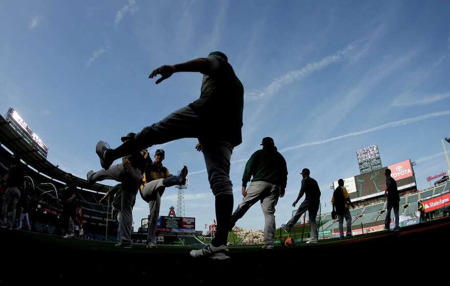 Members of the Oakland Athletics warm up before a baseball game against the Los Angeles Angels in Anaheim, Calif., Thursday, April 11, 2013. (AP Photo/Chris Carlson) Photo: Chris Carlson