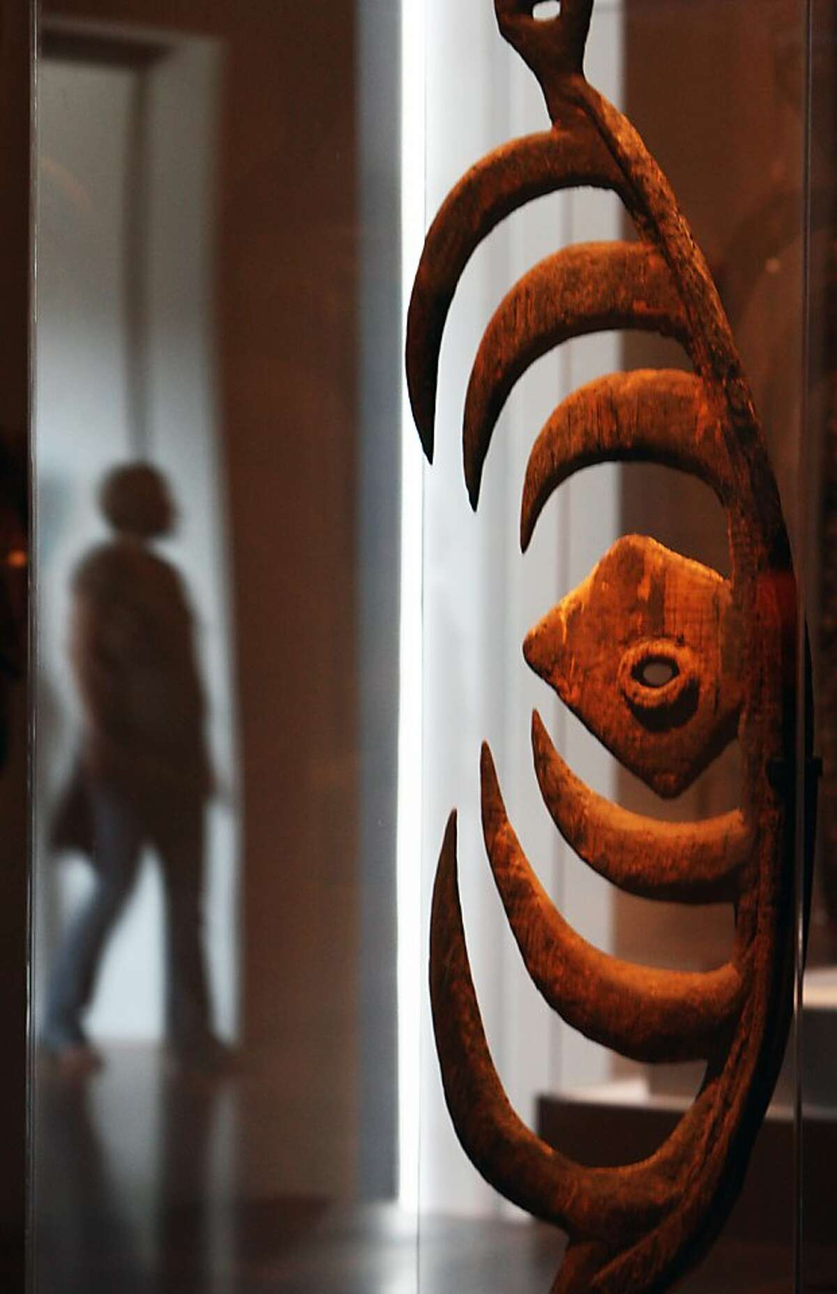 A visitor to the de Young Nuseum is reflected off the case housing a Cult Object, made by Bahinemo People from the Hunstein Mountains dated 18th-19th century. John Friede - a de Young trustee, donated the Jolika Collection of New Guinean art to the de Young Museum. The collection is now embroiled in an ownership dispute because a week after he gave the collection to the museum, he signed a paper giving the collection to his siblings who want to sell it off. There may also be a dispute from Papua New Guinea who might lay claim that the pieces were improperly taken from the country. Photographed in San Francisco Friday Sept 19, 2008.