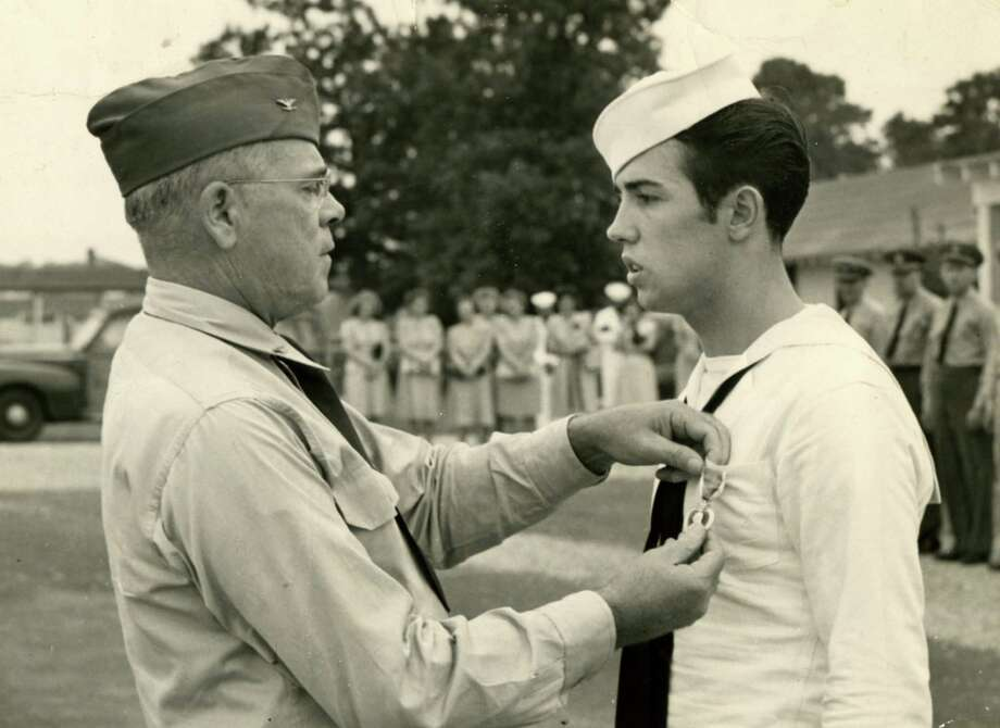 Navy Capt. H.V. Hughens pinning Purple Heart on Navy Signalman 2nd Class Bon Gusberti, right, at Naval Hospital, Fort Eustis, Va., in 1945. (U.S. Navy)