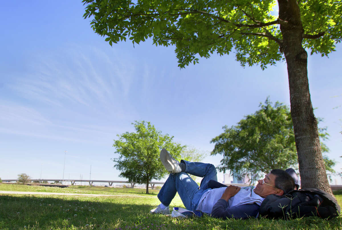 """Jerry Gamez relaxes under a tree in Stude Park on Friday in Houston. """"It's beautiful out here,"""" he said. """"It's not hot, it's not cold."""""""