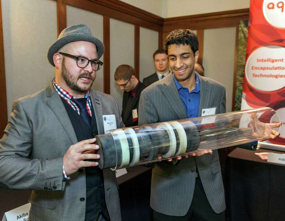"Rice competitors Nathan Chan, left, and Shaan Narang from the University of British Columbia demonstrate their ""agile monitoring equipment"" that is designed to use laser imaging to detect pinhole leaks in oil pipes before they get larger. Photo: Craig Hartley, Freelance / Copyright: Craig H. Hartley"