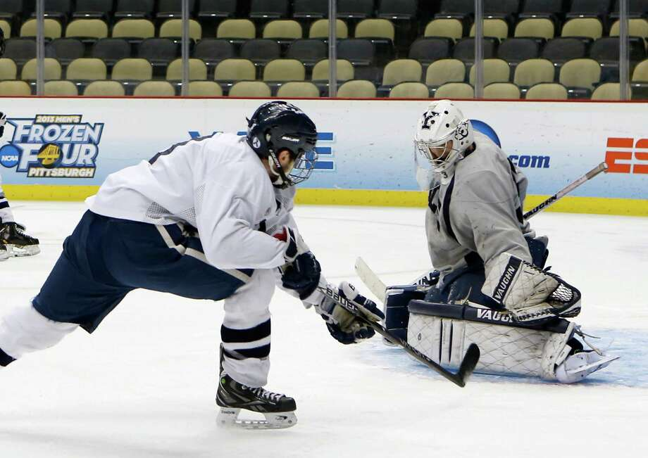 Yale's goalie Jeff Malcolm, right, looks to stop teammate Josh Balch during the team's practice session for the Frozen Four NCAA college hockey championship on Friday, April 12, 2013, in Pittsburgh. (AP Photo/Keith Srakocic) Photo: Keith Srakocic, Associated Press / AP