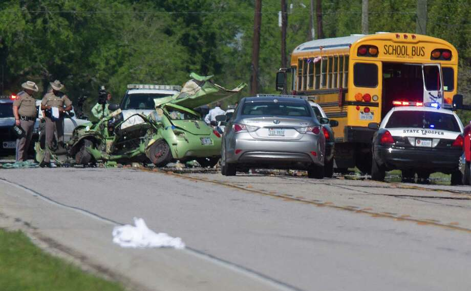 Officers investigate the scene where a driver died Friday morning when her Volkswagen Beetle collided with a Lamar Consolidated Independent School District bus in near Foster High School in Fort Bend County. Photo: Johnny Hanson, Staff / © 2013  Houston Chronicle
