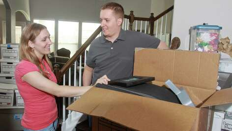 (For the Chronicle/Gary Fountain, April 1, 2013) Emily and Jay Ortiz unpacking in their new home in Richmond. They were shocked to find the Houston housing market so strong when they started looking. The couple and their two kids recently moved here from Salt Lake City. Theirs was one of multiple offers on a four-bedroom house in Lakes of Bella Terra in Richmond. In a second round of bidding they offered $5,000 more than the asking price to get the house.