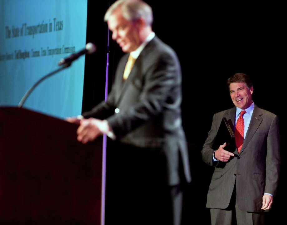 Ahead of his speech Friday, Gov. Rick Perry, right, is introduced by Ted Houghton, chairman of the Texas Transportation Commission, in Austin. Photo: Ricardo Brazziell, MBO / AUSTIN AMERICAN-STATESMAN