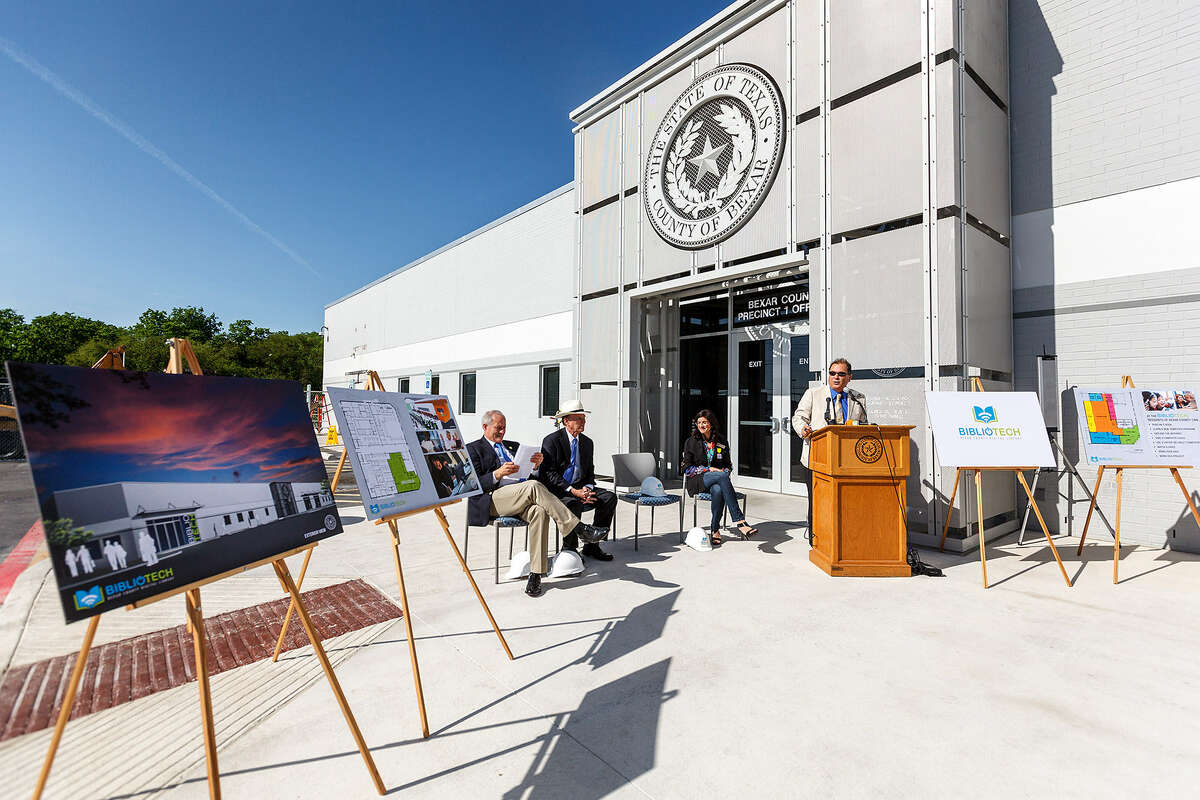 """County Commissioner Tommy Adkisson (seated, from left), County Judge Nelson Wolff, and City Councilwoman Leticia Ozuna listen as County Commissioner Sergio """"Chico"""" Rodriguez speaks during a ceremony for BiblioTech, the base for the nation's first public library system without paper books, at the county's South Side service center on Pleasanton Road."""